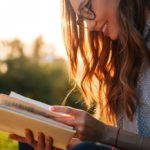 Smiling brunette woman in eyeglasses reading book