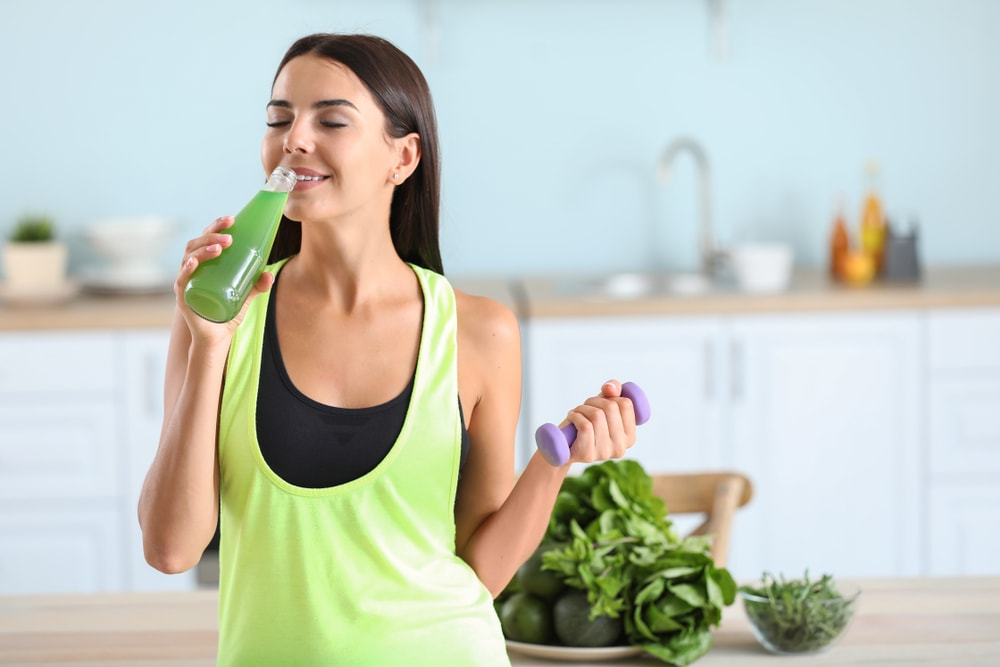 Sporty woman drinking healthy vegetable juice